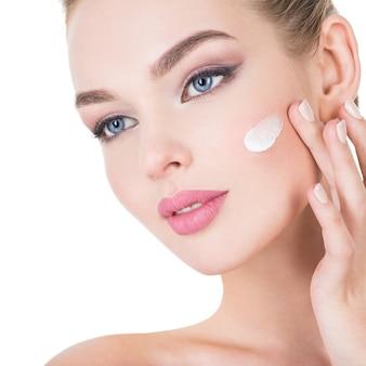 Mulher jovem aplica creme cosmético no rosto.