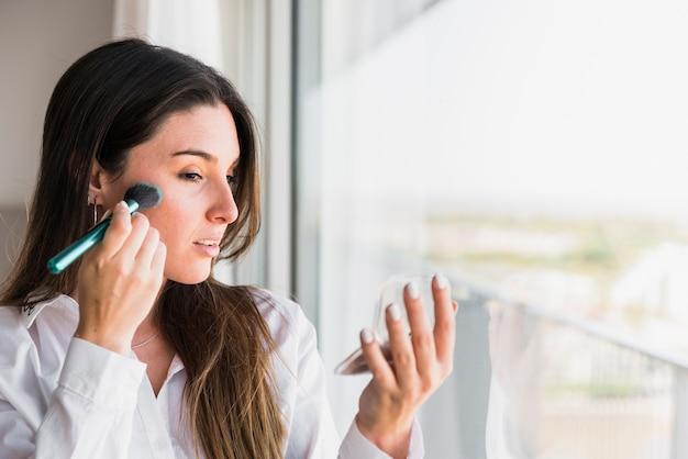 Mulher jovem, aplicando, a, pó compacto, com, escova maquiagem