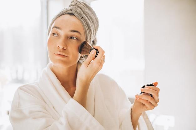 Mulher jovem aplicando blush e olhando no espelho