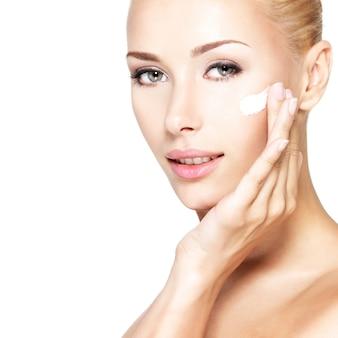 Mulher jovem aplicando creme cosmético em um rosto limpo e fresco