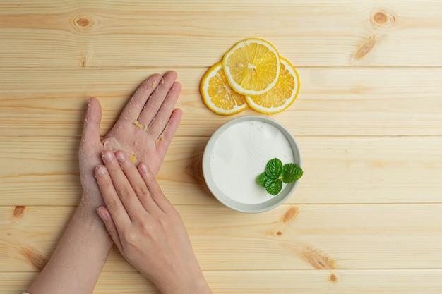 Mulher jovem aplicando esfoliante natural de limão nas mãos contra uma mesa de madeira
