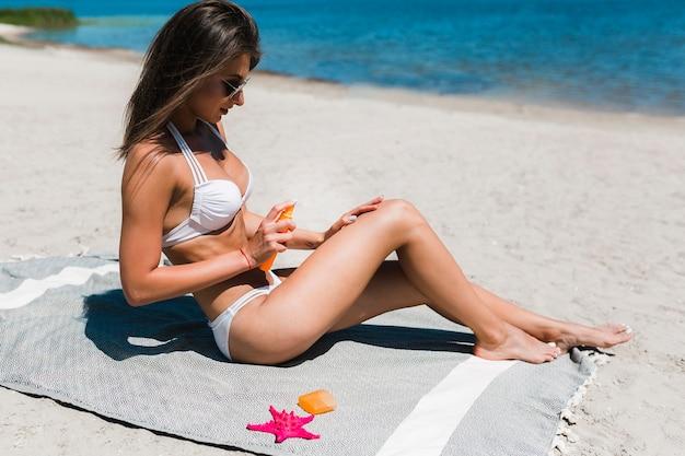 Mulher jovem, aplicando lotion suntan, ligado, perna