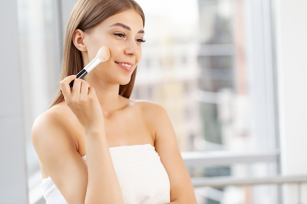 Mulher jovem aplicando maquiagem no rosto em casa