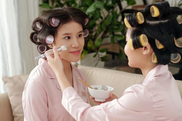 Mulher jovem aplicando máscara de argila no rosto bonito de sua melhor amiga enquanto elas estão curtindo a festa de beleza em casa