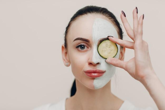 Mulher jovem aplicando máscara de argila no rosto com pepino nos olhos em spa de beleza