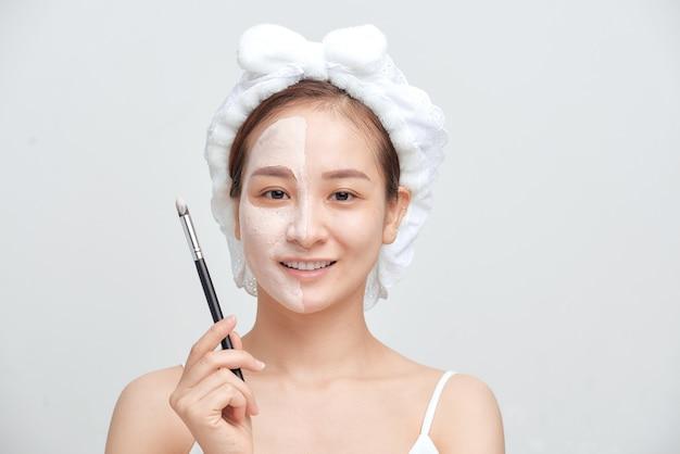 Mulher jovem aplicando máscara facial de argila de lama no rosto, sobre fundo branco