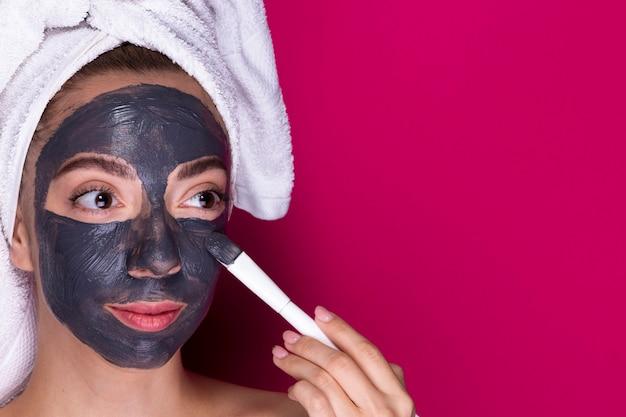 Mulher jovem, aplicando máscara facial Foto gratuita