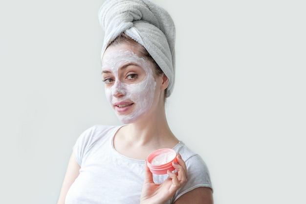 Mulher jovem aplicando máscara nutritiva branca ou creme no rosto isolado no branco