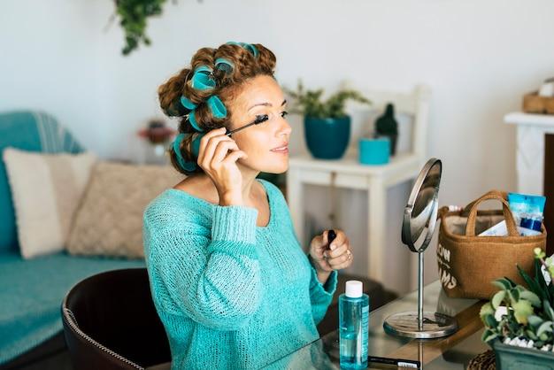 Mulher jovem aplicando rímel nos cílios enquanto se olha no espelho na sala de estar de casa