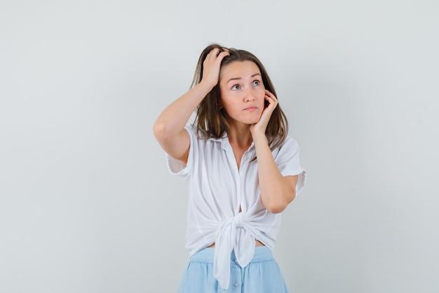 Mulher jovem apoiando a bochecha na palma da mão enquanto coça a cabeça com blusa branca e saia azul claro e parece alegre