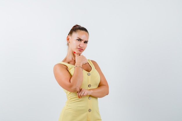 Mulher jovem, apoiando o queixo no dedo em um vestido amarelo e parecendo preocupada. vista frontal.