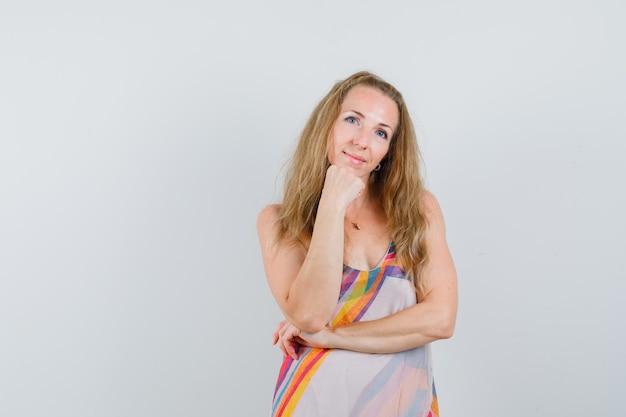 Mulher jovem apoiando o queixo no punho levantado em um vestido de verão e parecendo calada