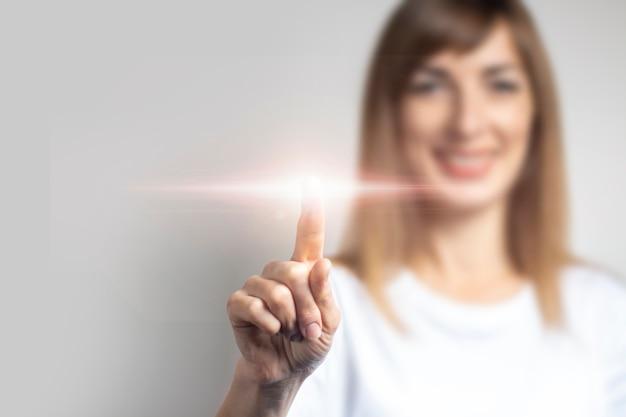 Mulher jovem aponta e pressiona um dedo em uma tela virtual