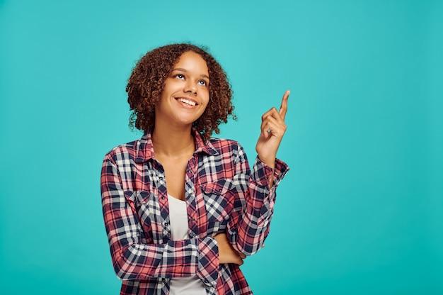 Mulher jovem aponta para cima, parede azul, emoção positiva. expressão facial, pessoa do sexo feminino olhando para a câmera no estúdio, conceito emocional, sentimentos
