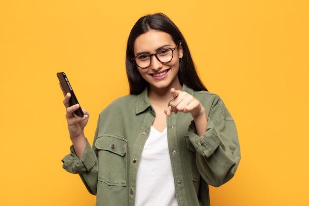 Mulher jovem apontando com um sorriso satisfeito, confiante e amigável