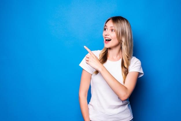 Mulher jovem apontando o dedo para o lado sobre uma parede azul isolada