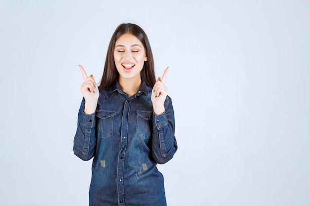 Mulher jovem apontando ou apresentando algo em ambos os lados