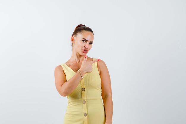 Mulher jovem apontando para a direita em um vestido amarelo e parecendo indecisa