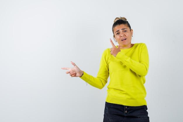 Mulher jovem apontando para a esquerda com o dedo indicador em um suéter amarelo e calça preta e parecendo feliz