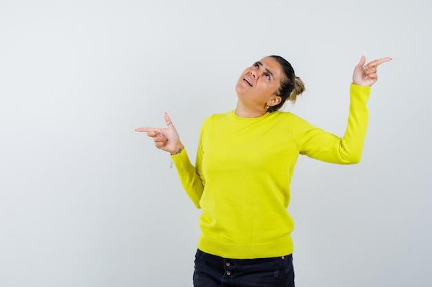 Mulher jovem apontando para a esquerda e para a direita com os dedos indicadores em um suéter amarelo e calça preta e parecendo atormentada