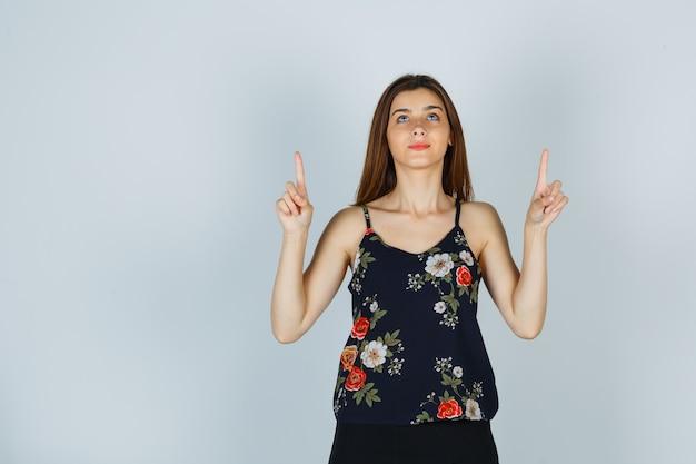 Mulher jovem apontando para cima com um top floral e parecendo sonhadora