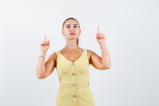 Mulher jovem apontando para cima, olhando para cima com um vestido amarelo e parecendo esperançosa