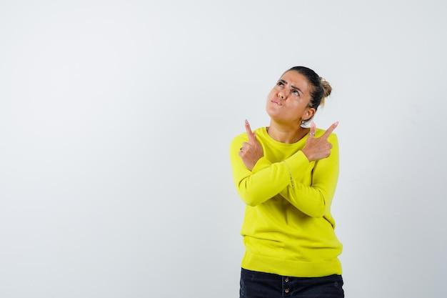 Mulher jovem apontando para direções opostas com um suéter amarelo e calças pretas e olhando focada