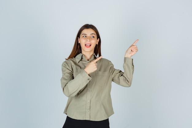 Mulher jovem apontando para o canto superior direito de camisa, saia e parecendo feliz