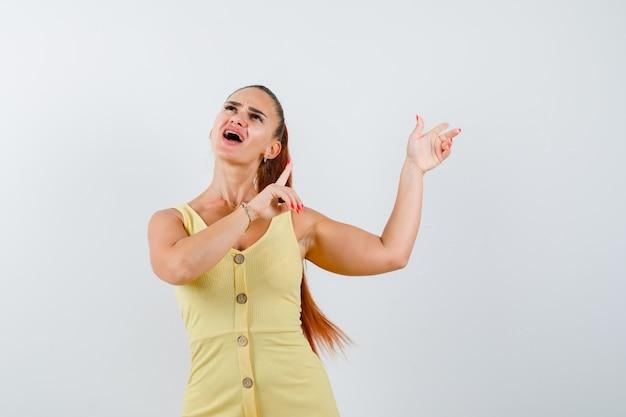 Mulher jovem apontando para o canto superior direito, olhando para cima com um vestido amarelo e parecendo confusa