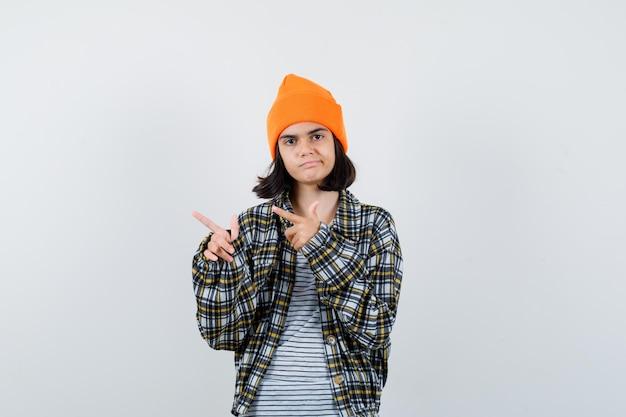 Mulher jovem apontando para o lado com uma camisa quadriculada de chapéu laranja parecendo infeliz