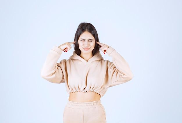 Mulher jovem apontando para o ouvido quando a voz é alta ou baixa