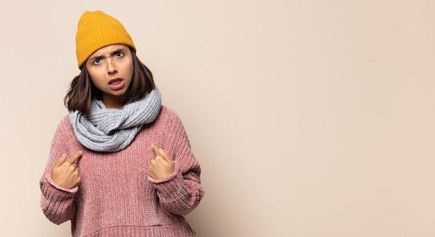 Mulher jovem apontando para si mesma com os dois dedos e expressão de raiva, dizendo para você cumprir seu dever