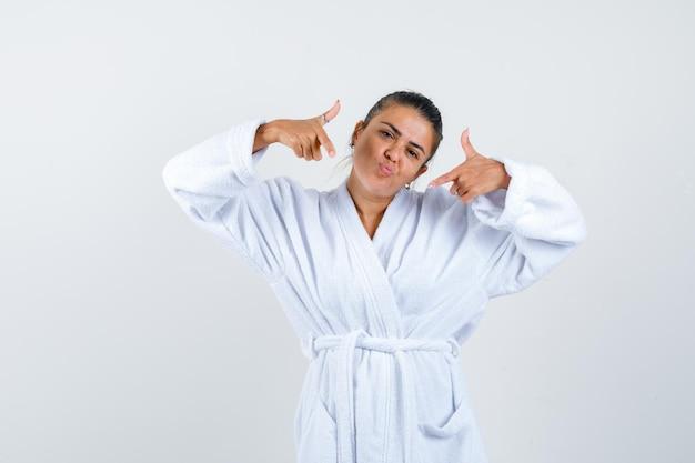 Mulher jovem apontando para si mesma com um roupão de banho e parecendo orgulhosa