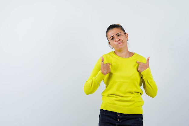 Mulher jovem apontando para si mesma, fazendo uma careta em um suéter amarelo e calças pretas e parecendo preocupada
