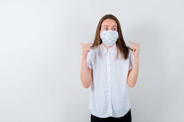 Mulher jovem apontando para sua máscara médica