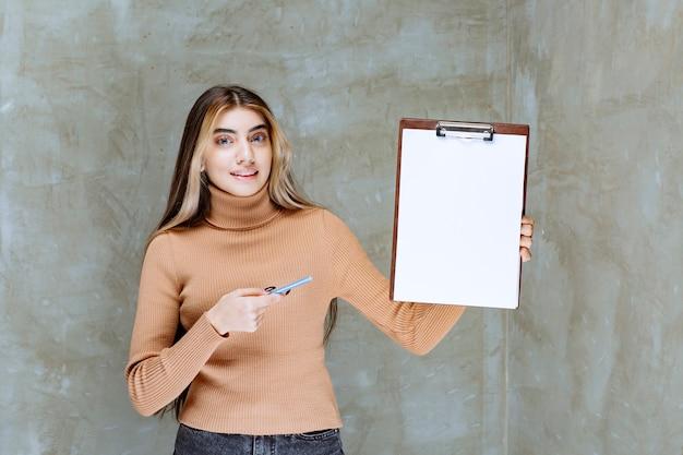 Mulher jovem apontando para um bloco de notas vazio com uma caneta sobre uma pedra