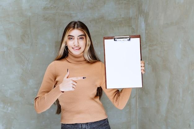 Mulher jovem apontando para um bloco de notas vazio em uma pedra