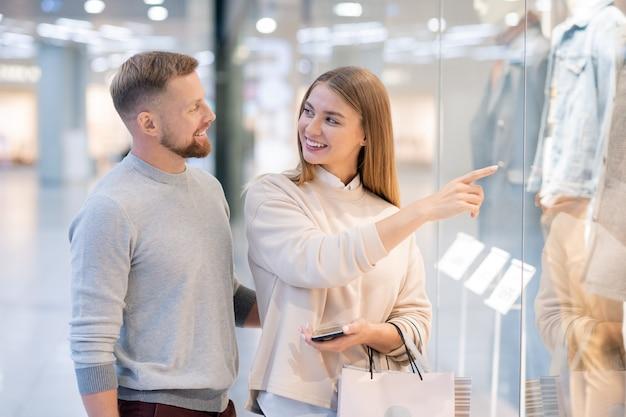 Mulher jovem apontando para um casaco da nova coleção sazonal na vitrine enquanto olha para o marido com um sorriso durante as compras