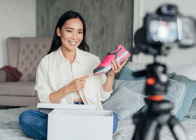 Mulher jovem apontando para um tênis enquanto faz um vlog