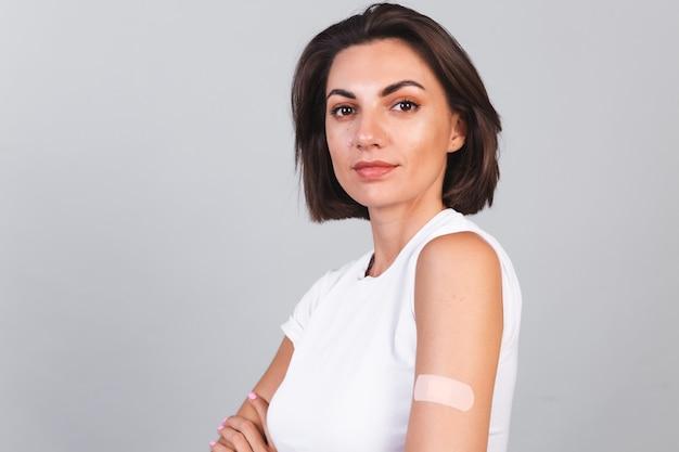 Mulher jovem após a vacinação, mostrando o braço com bandagem de gesso. proteção contra vírus. covid-2019.
