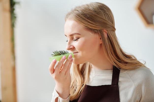 Mulher jovem apreciando o cheiro de conífera fresca em cima de uma barra de sabonete verde artesanal após terminar o trabalho criativo