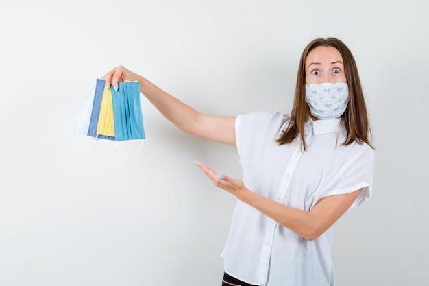 Mulher jovem apresentando máscaras médicas