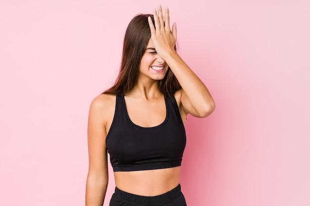 Mulher jovem aptidão caucasiana fazendo esporte isolado esquecendo algo, batendo na testa com a palma da mão e fechando os olhos.