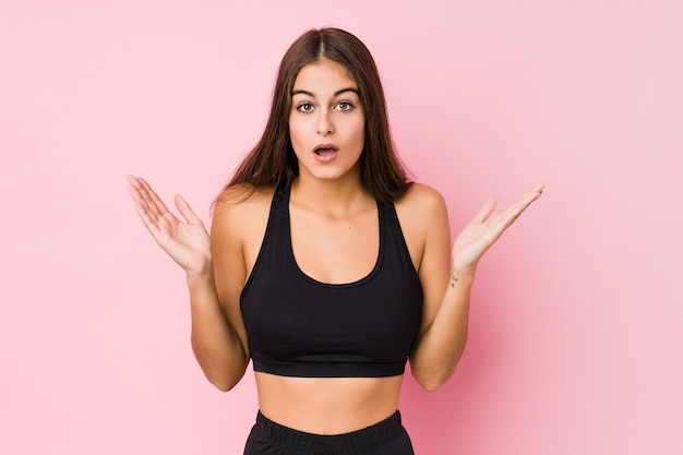 Mulher jovem aptidão caucasiana fazendo esporte isolado surpresa e chocada.