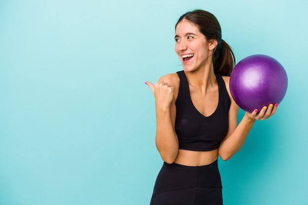 Mulher jovem aptidão caucasiana segurando uma bola isolada em pontos de fundo azul com o dedo polegar afastado, rindo e despreocupada.