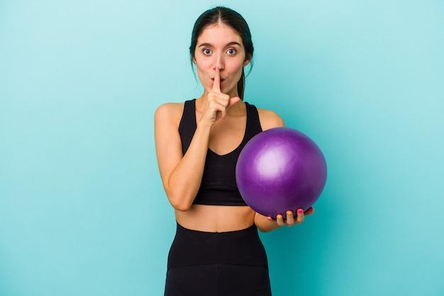 Mulher jovem aptidão caucasiana segurando uma bola isolada em um fundo azul, mantendo um segredo ou pedindo silêncio.