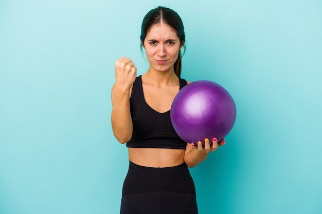 Mulher jovem aptidão caucasiana segurando uma bola isolada em um fundo azul, mostrando o punho para a câmera, expressão facial agressiva.