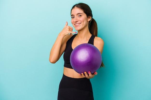 Mulher jovem aptidão caucasiana segurando uma bola isolada em um fundo azul, mostrando um gesto de chamada de telefone móvel com os dedos.