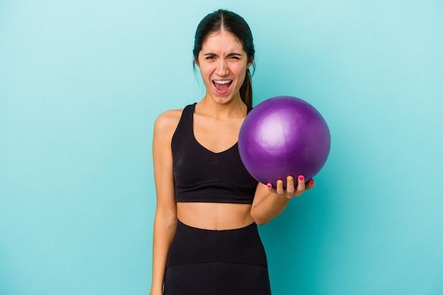 Mulher jovem aptidão caucasiana segurando uma bola isolada no fundo azul, gritando muito zangada e agressiva.