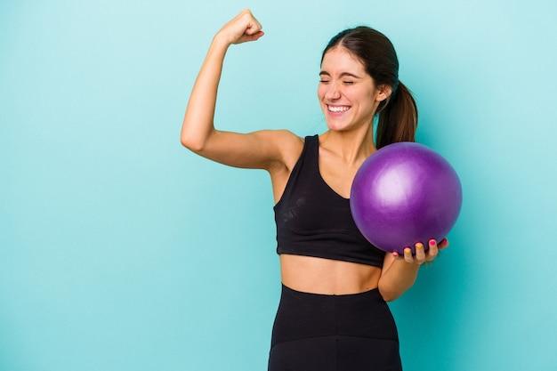 Mulher jovem aptidão caucasiana segurando uma bola isolada no fundo azul, levantando o punho após uma vitória, o conceito de vencedor.